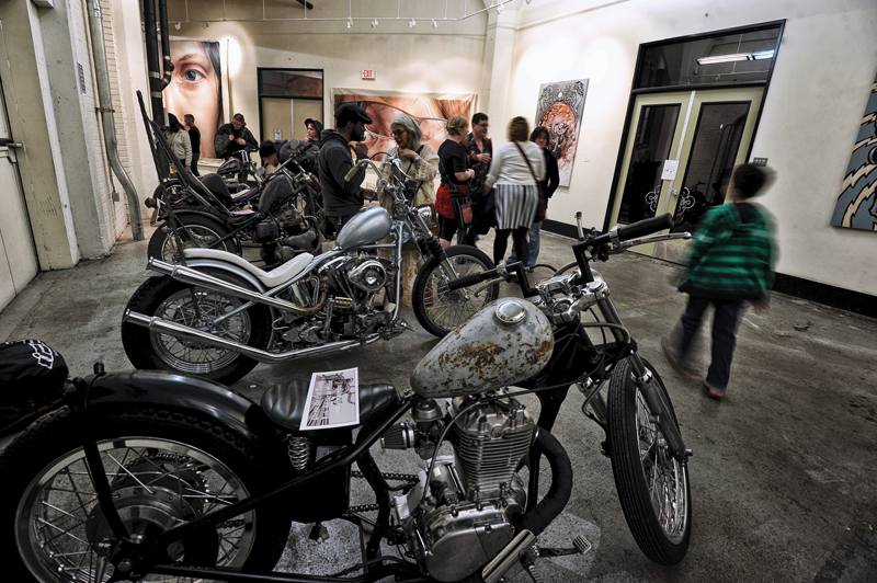 A view of the exhibit with Tony Morgan's motorcycles. In the background are Coatney's paintings and one of Morgan's paintings to the right of the frame.