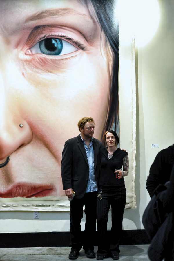 Left to right: Painter Jason Coatney with artist Emily Kosta in front of Coatney's painting of Kosta.