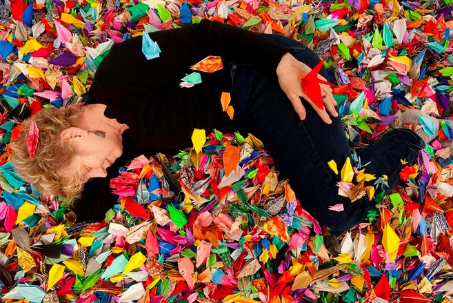 Patrice Demmon lounges in her folded paper cranes